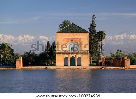 Morocco Marrakesh  Menara Pavilion and  Gardens reflected on the lake in late afternoon sunshine with snow covered peaks of the Atlas Mountains in the background - stock photo