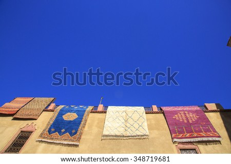 Morocco, Marrakesh, typical colourful Moroccan Berber carpets hanging on display from a wall. - stock photo