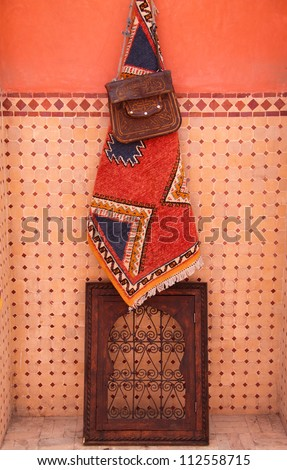 Morocco, Marrakesh, Typical handy-craft articles on display against a colourful tiled wall in the Medina souk - woollen carpet, leather satchel and decorative wooden and wrought iron miniature window. - stock photo