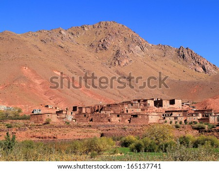 Morocco, Ouarzazate -  Typical Berber village built in adobe and stone in the High Atlas Mountains near Ait Ben Haddou, UNESCO World Heritage site.  - stock photo