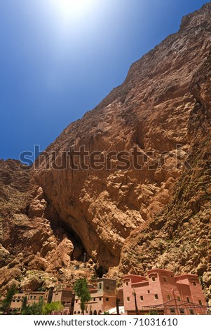 Morocco. Todra Gorge with 300 m high rock walls - a few of houses located in a narrow point of the gorge - stock photo