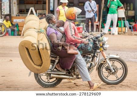 Morogoro, Tanzania: April 22: A woman holding a child and an old matress hires a bodaboda (Motorcycle) taxi  on April 22, 2015 in Morogoro, Tanzania - stock photo