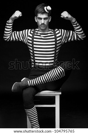 Morose circus performer sitting in a striped dress - stock photo