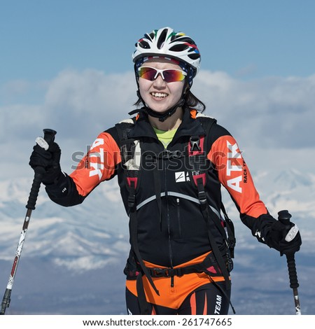 MOROZNAYA MOUNT, KAMCHATKA, RUSSIA - APRIL 25, 2014: Chinese ski mountaineer Ma Nan climb on skis on mountain. Vertical race ski mountaineering Asian, ISMF, Russian, Kamchatka Championship. - stock photo