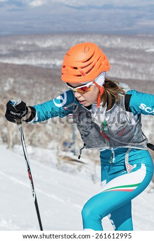MOROZNAYA MOUNT, KAMCHATKA, RUSSIA - APRIL 25, 2014: Ski mountaineer Catherine Osichkina climb on skis on mountain. Vertical race ski mountaineering Asian, ISMF, Russian, Kamchatka Championship. - stock photo