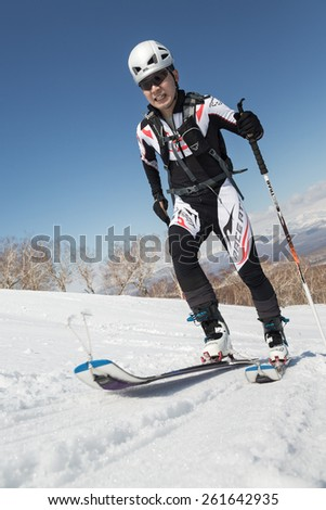 MOROZNAYA MOUNT, KAMCHATKA, RUSSIA - APRIL 25, 2014: Ski mountaineer climb on skis on Moroznaya Mountain. Vertical race ski mountaineering Asian, ISMF, Russian, Kamchatka Championship. - stock photo