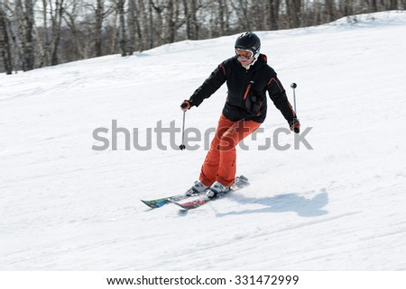 MOROZNAYA MOUNTAIN, YELIZOVO, KAMCHATKA, RUSSIA - APRIL 17, 2015: Young woman skier coming down the slope on a sunny day. Kamchatka Peninsula, Far East, Russian Federation. - stock photo