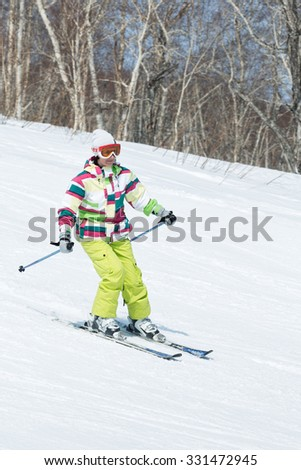 MOROZNAYA MOUNTAIN, YELIZOVO, KAMCHATKA, RUSSIA - APRIL 17, 2015: Young woman skier in colorful outfit coming down the slope on a sunny day. Kamchatka Peninsula, Far East, Russian Federation. - stock photo