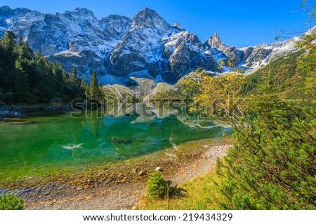 Morskie Oko lake in autumn colours with fresh snow covered peaks, High Tatra Mountains, Poland - stock photo