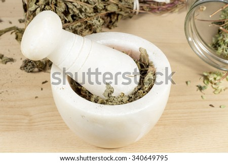 Mortar and pestle made of white marble, beside dry herbs (pennyroyal and oregano) - stock photo