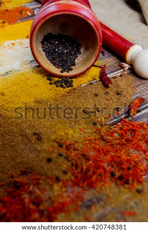 Mortar and pestle near white spoon with different of spices scattered on the wooden table, top view. different dry spices on a wooden background. Closeup