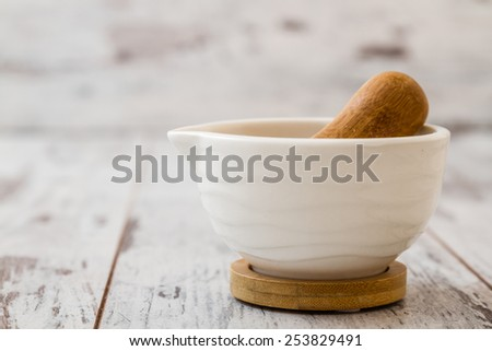 Mortar and pestle set on white wooden background - stock photo
