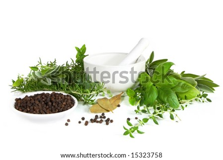 Mortar and pestle with fresh herbs and peppercorns.   Isolated on white.