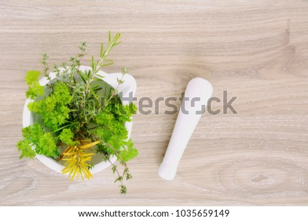 Mortar and pestle with fresh herbs in flat lay format and shot in natural light