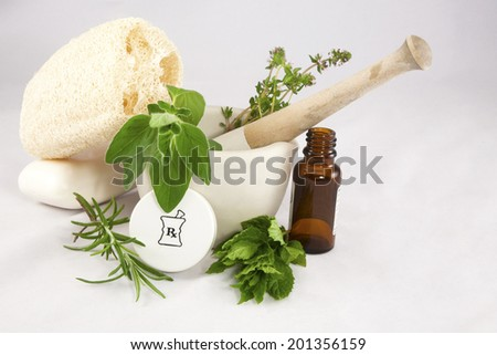 Mortar and Pestle with fresh mint, thyme, rosemary and sage with prescription bottle cap, vial, soap louffa. - stock photo