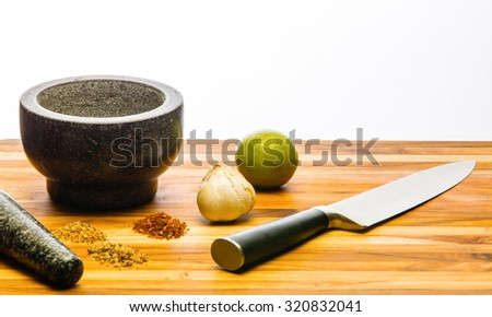 Mortar and pestle with garlic and lime on a cutting board with custom ground spices and a large kitchen knife - stock photo