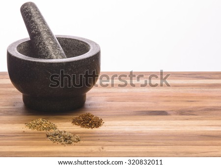 Mortar and pestle with handmade spices on a wooden cutting board - stock photo