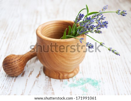 Mortar and pestle with lavender on a wooden background - stock photo
