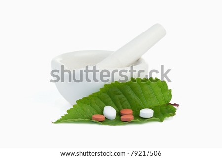 Mortar and pestle with pills on a leaf against a white background - stock photo