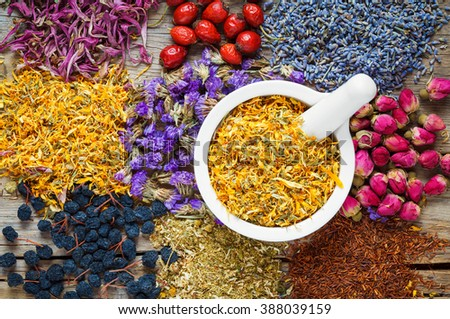 Mortar of dry marigold flowers, healthy herbs, herbal tea assortment and berries on old wooden table. Herbal medicine. - stock photo