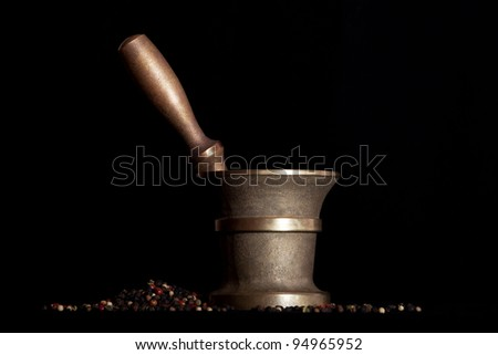 Mortar, pestle and pepper mixture on dark background