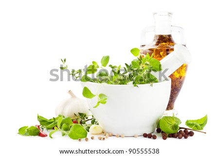 Mortar with fresh green herbs, spices, garlic and a bottle of olive oil - stock photo