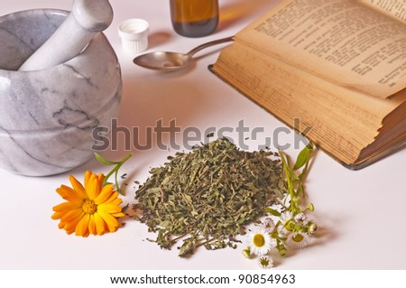mortar with herbs and tincture - stock photo