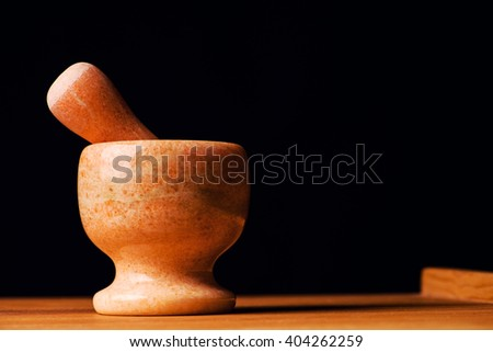 Mortar with pestle isolated on black background - stock photo