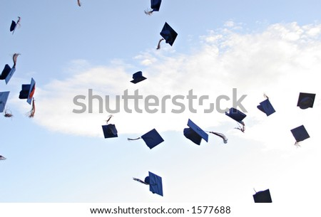 Mortarboards fly in air at graduation