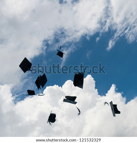 Mortarboards  in the air at graduation.