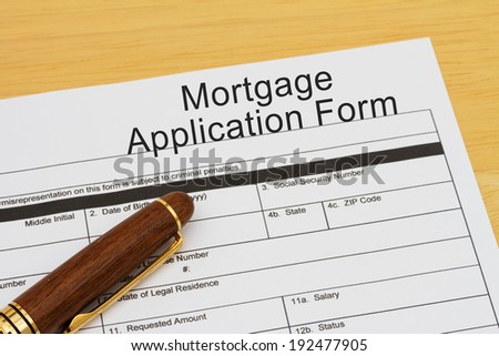 Mortgage Application Form with a pen on a wooden desk