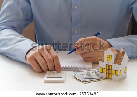 Mortgage concept. Businessmen counting on calculator and sitting at the table with small toy house, cash, and notebook - stock photo