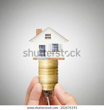 Mortgage concept by money house from  coins in hand - stock photo