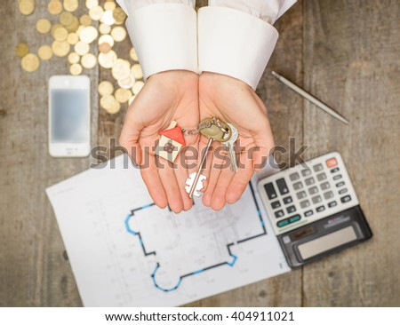 Mortgage concept. Real estate agent handing over a house key, desktop with tools, wood swatches and computer on wooden background, top view - stock photo