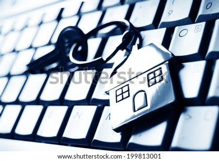Mortgage concept with keys and house-shaped key ring on laptop keyboard - stock photo