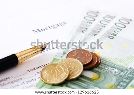 mortgage contract, pen and coins isolated on white background