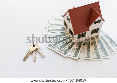 mortgage, investment, real estate and property concept - close up of home model, dollar money and house keys - stock photo