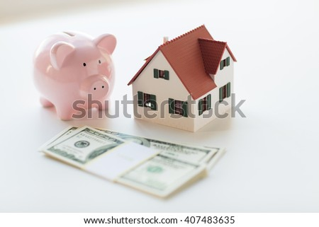 mortgage, investment, real estate and property concept - close up of home or house model, us dollar money and piggy bank - stock photo