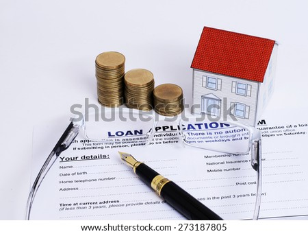 Mortgage loans concept with Fountain pen and eyeglasses and paper house and coins stack on Loan Application form