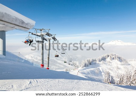 MORZINE, FRANCE - FEBRUARY 06, 2015: Skiers and snow boarders on the Ranfoilly Express chair lift at the top of Le Ranfoilly peak in Les Gets ski resort, part of the Portes du Soleil ski area. - stock photo