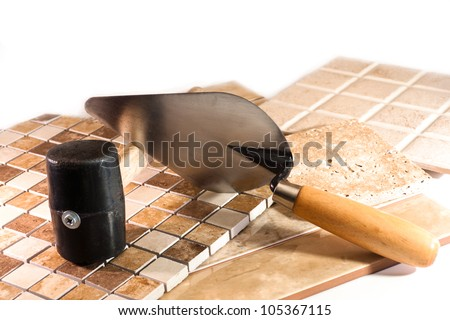 Mosaic of colored marble, rubber mallet and trowel for laying ceramic tile - stock photo