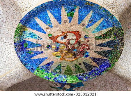 Mosaic sun medallion at the Parc Guell designed by Antoni Gaudi located on Carmel Hill, Barcelona, Spain. - stock photo