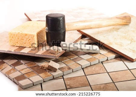 Mosaic tiles of marble and ceramics, rubber mallet, and sponge - stock photo