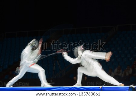 MOSCOW - APR 6: Fight in motion on championship of world in fencing among juniors and cadets, in Sports Olympic complex, on April 6, 2012 in Moscow, Russia - stock photo