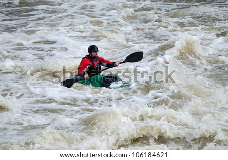 "MOSCOW - APRIL 14: An unidentified kayaker trains whitewater rafting technique at Pakhra river during a traditional spring meeting ""Pakhra 2012"" on April 14, 2012 in Moscow, Russia."