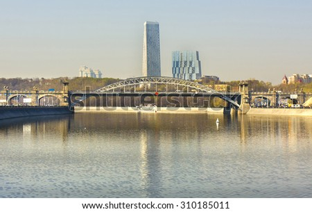 MOSCOW - APRIL 21, 2014: Andreevsky (Pushkinsky) bridge on Moskva-river, has been built in 1999, and modern skyscrapers. - stock photo