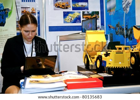 MOSCOW - APRIL 13: Girl with laptop, mining equipment at the international exhibition of  the Mining and Processing of Metals and Minerals, MiningWorld on April 13, 2011 in Moscow - stock photo