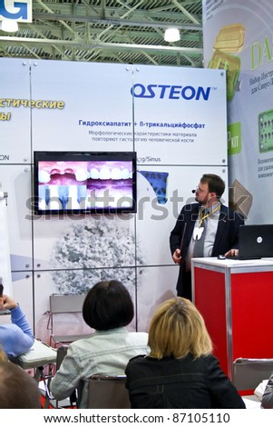 MOSCOW - APRIL 27: Man tells of prosthetics at the international exhibition of the dental professionals and industry on April 27, 2011 in Moscow - stock photo