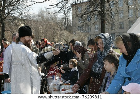 MOSCOW - APRIL 23: Orthodox priest splatters holy water on Easter cakes at the celebration of Orthodox Easter in Russia on April 23, 2011 in Moscow, Russia.