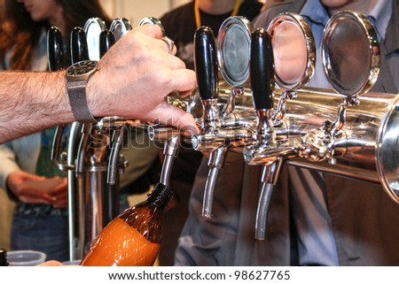 MOSCOW-APRIL 27: Pouring beer to glass from beer tap at the international exhibition of market production beer, and low alcohol drinks Brewer on April 27, 2011 in Moscow - stock photo